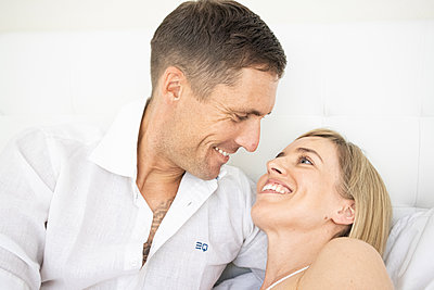 Happy couple sitting on bed, portrait - p1640m2259612 by Holly & John