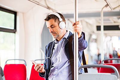 Businessman with smartphone and headphones travelling by bus - p300m1469812 by HalfPoint