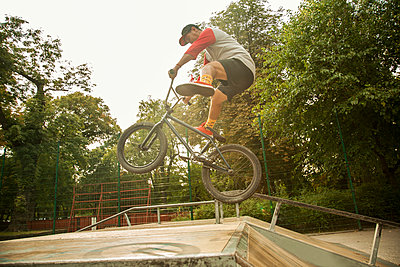 Young male BMX biker performing mid-air stunt at skateboard park - p300m2225018 by LOUIS CHRISTIAN