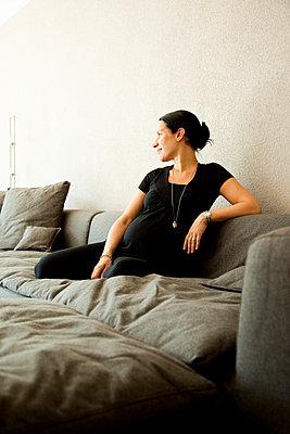 Woman sitting in sofa, looking away - p4267747f by Tuomas Marttila