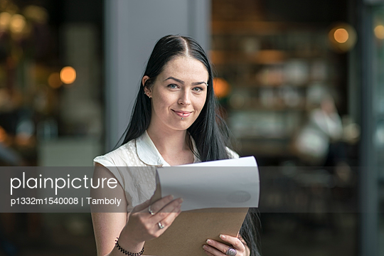 Young businesswoman holding a check list - p1332m1540008 by Tamboly