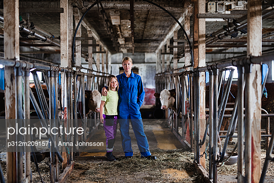 Woman and daughter in cowshed - p312m2091571 by Anna Johnsson
