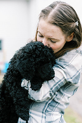 Woman holding her black new cute poodle puppy in arms lovingly - p1166m2236788 by Cavan Images