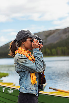 Finland, Lapland, woman taking picture with a camera at the lakeside - p300m2060772 von Kike Arnaiz