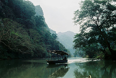 A barge sails on the river leading to Nguom Ngao Cave, Cao Bang province, Vietnam, Southeast Asia - p934m1177414 by Dzung Le photography