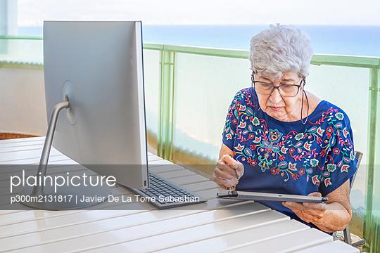 Senior woman using computer on the terrace - p300m2131817 by Javier De La Torre Sebastian
