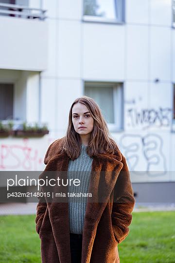 Junge Frau vor Plattenbau - p432m2148015 von mia takahara