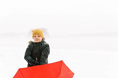 Little boy holding his umbrella. - p1166m2157459 by Cavan Images