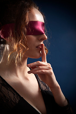 Woman with Blindfold with Finger on Lips - p1248m2063464 by miguel sobreira