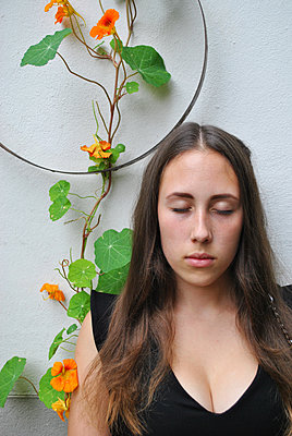 Teenage girl with plunging neckline and nasturtium abloom - p1648m2228479 by KOLETZKI