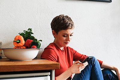 Woman sitting in kitchen, checking smartphone messages - p300m1588064 von Florian Küttler