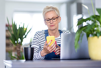 Businesswoman using smart phone at desk in home office - p300m2293966 by William Perugini