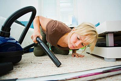 Woman lying on the floor - p4263722f by Tuomas Marttila