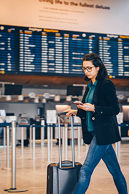 Businesswoman using mobile phone while walking with luggage in airport terminal - p426m1580061 by Maskot