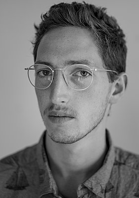 Portrait of young man with eyeglasses - p552m2214906 by Leander Hopf