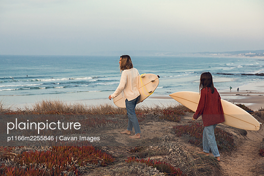 Two Surfer girls going surf - p1166m2255846 by Cavan Images