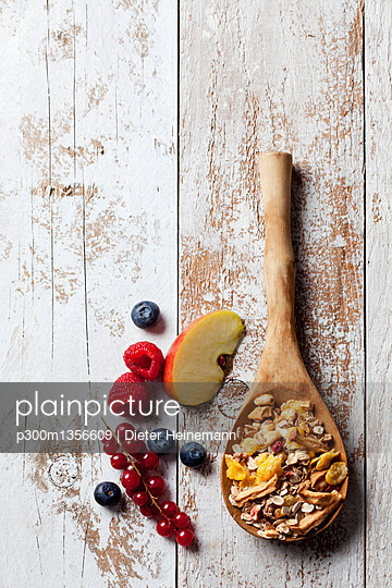 Wooden spoon of granola with dried fruits and various fresh fruits on wood - p300m1356609 by Dieter Heinemann
