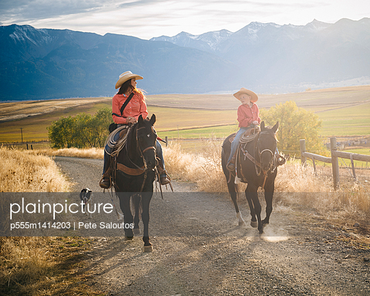 Caucasian mother and son riding horses on ranch - p555m1414203 by Pete Saloutos