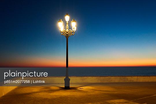 Straßenlaterne bei Sonnenuntergang auf der Uferpromenade - p851m2077258 von Lohfink