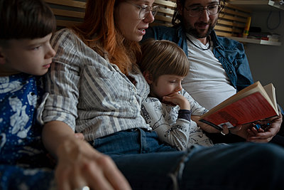Family reading bedtime story book - p1192m1567332 by Hero Images