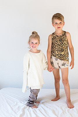 Geschwister halten Händchen und lachen in die Kamera - p1301m1465626 von Delia Baum