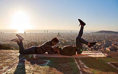 Romantic gay men with face to face lying on observation point during sunrise, Bunkers del Carmel, Barcelona, Spain - p300m2256691 by Veam