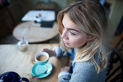 Young woman sitting in cafe, holding tea cup, thoughtful expression on face - p429m1206892 by Janeycakes Photos