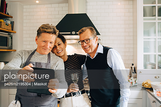 Smiling man taking selfie with friends standing in kitchen at home - p426m2195304 by Maskot