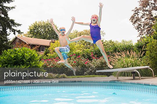 Caucasian children jumping into swimming pool - p555m1421666 by JGI/Jamie Grill