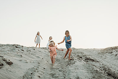 Four young sisters running in sand at beach sunset - p1166m2165910 by Cavan Images
