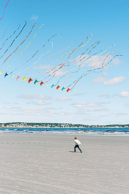 A boy chasing a large kite flying past him on a New England beach - p1166m2212934 by Cavan Images
