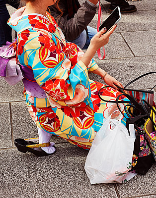 Frau in Kimono benutzt Smartphone - p1397m2054700 von David Prince