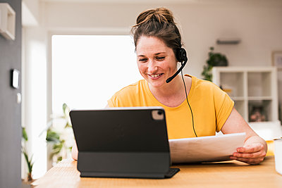 Smiling businesswoman wearing headphones video conferencing at home - p300m2268189 by Uwe Umstätter