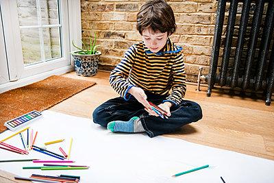 Boy sitting on floor drawing on long paper - p429m1407824 by Bonfanti Diego