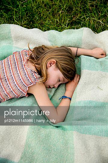 Mädchen schläft auf der Decke im Garten - p1212m1145986 von harry + lidy