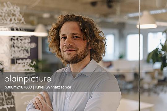 Portrait of confident businessman behind a glass pane in office - p300m2167330 von Kniel Synnatzschke