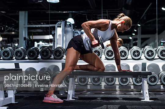 Woman Doing Bicep Exercise In Gym   - p847m2104949 by Evelina Rönnbäck