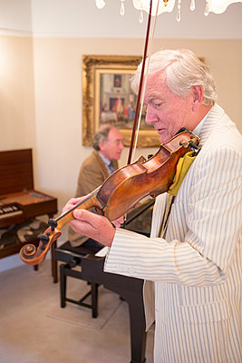 Two senior men playing music together - p1026m1164194 by Patrick Frost