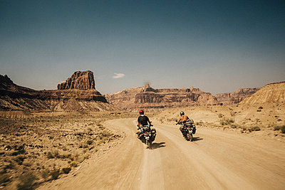 Rear view of friends riding motorbikes on dirt road against sky during sunny day - p1166m1521774 by Cavan Images