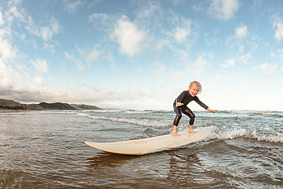Young child surfing on a surfboard on a sunny day at a beach - p1166m2108129 by Cavan Images