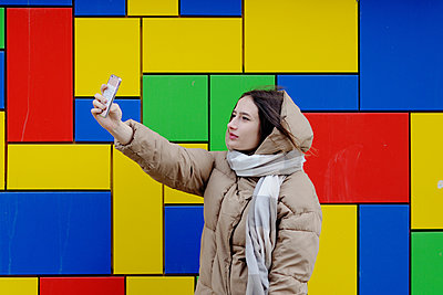 Young woman in a winter jacket against bright wall - p1412m2054339 by Svetlana Shemeleva