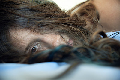 Young woman lying in bed with hair covering her face - p1580m2191508 by Andrea Christofi