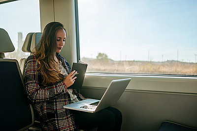Businesswoman on a train with notebook and laptop - p300m1205135 by Kiko Jimenez