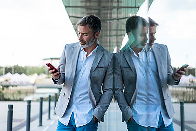 Businessman leaning against glass facade using smartphone - p300m2012298 by VITTA GALLERY