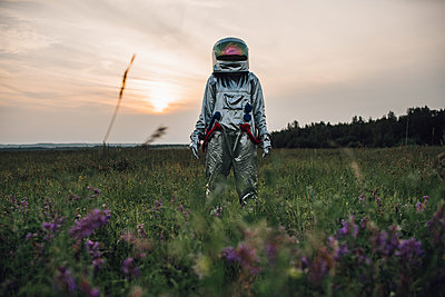 Spaceman exploring nature, standing in meadow, - p300m2030558 by Vasily Pindyurin