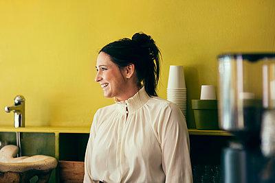 Happy waitress looking away in coffee shop - p426m1176527 by Maskot