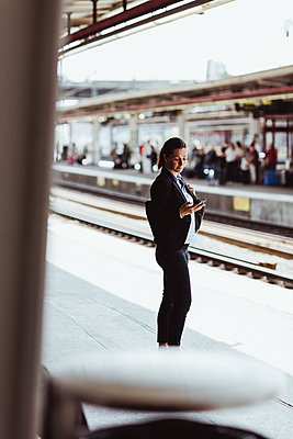 Businesswoman using mobile phone while standing at railroad station platform - p426m2146206 by Maskot