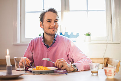 Portrait of man smiling while eating pasta - p426m896850f by Maskot