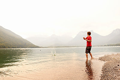 Young man skimming stone in Lake Annecy, Annecy, Rhone-Alpes, France - p429m2074424 by Ross Woodhall