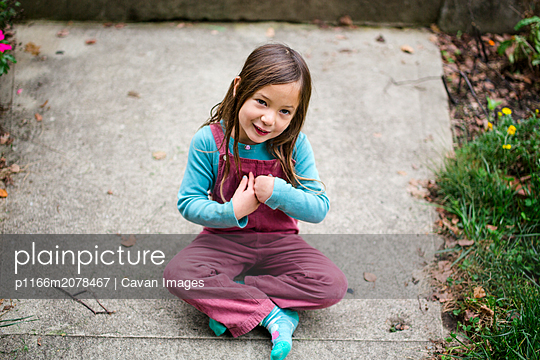 cute little girl looking up smiling while sitting on the sidewalk - p1166m2078467 by Cavan Images